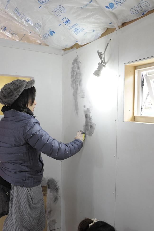 スポンジを使って白い壁の上に黒い塗料を重ねていく